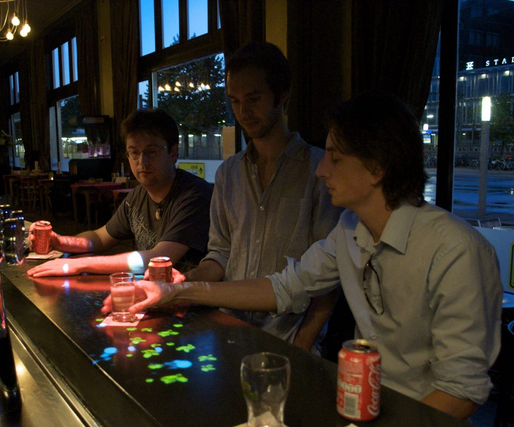 Anemone, an emergent entertaining ambient interactive bar installation.  This system aims to spontaneously  entertain people at the bar and bring them into contact with each other by projecting an interactive virtual ecosystem.
